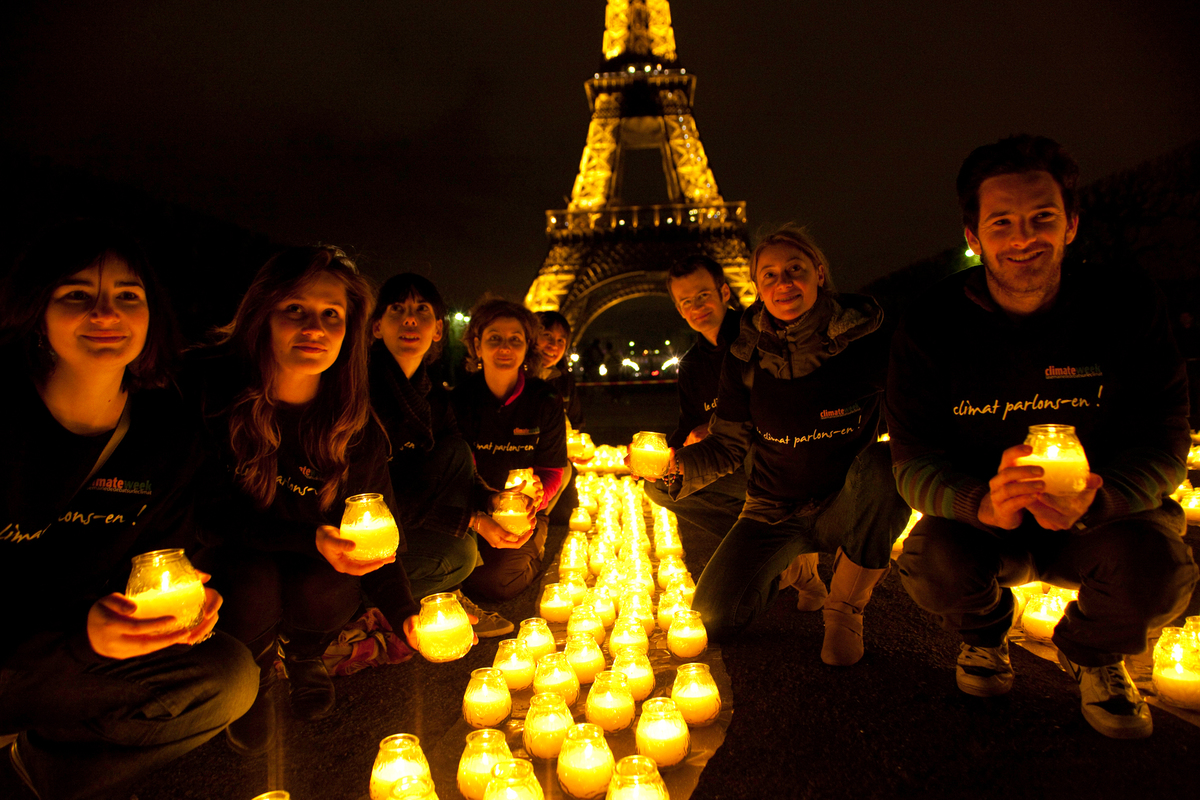Earth Hour 2010. 8 french WWF volunteers holding candles by the Eiffel Tower