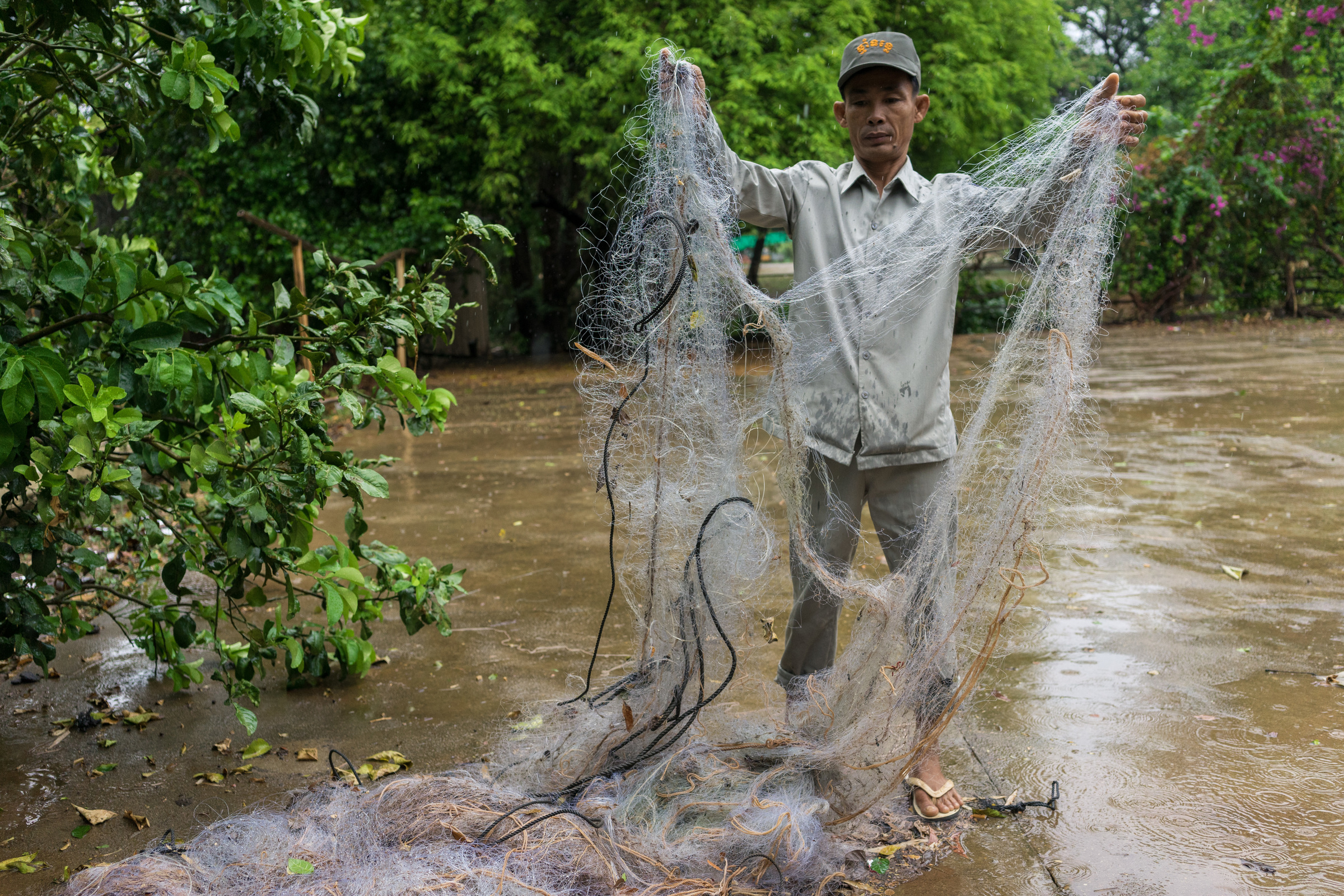 A river guard holds up confiscated gillnets, Mekong