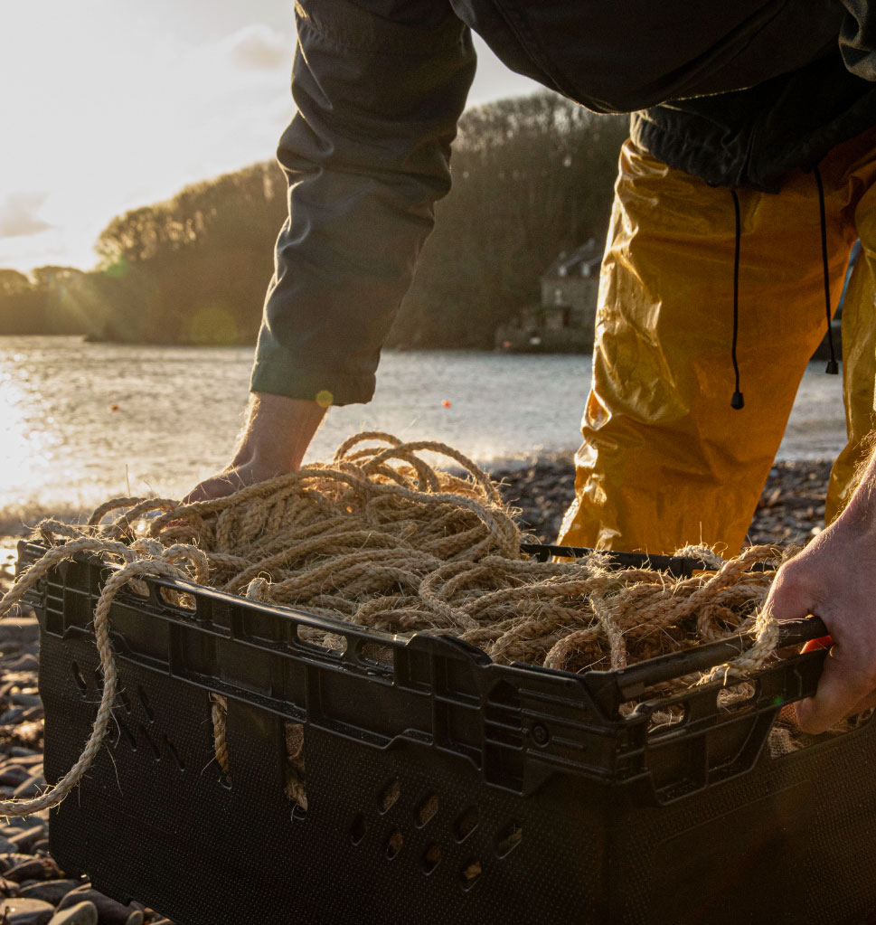 Man picking up a basket of ropes