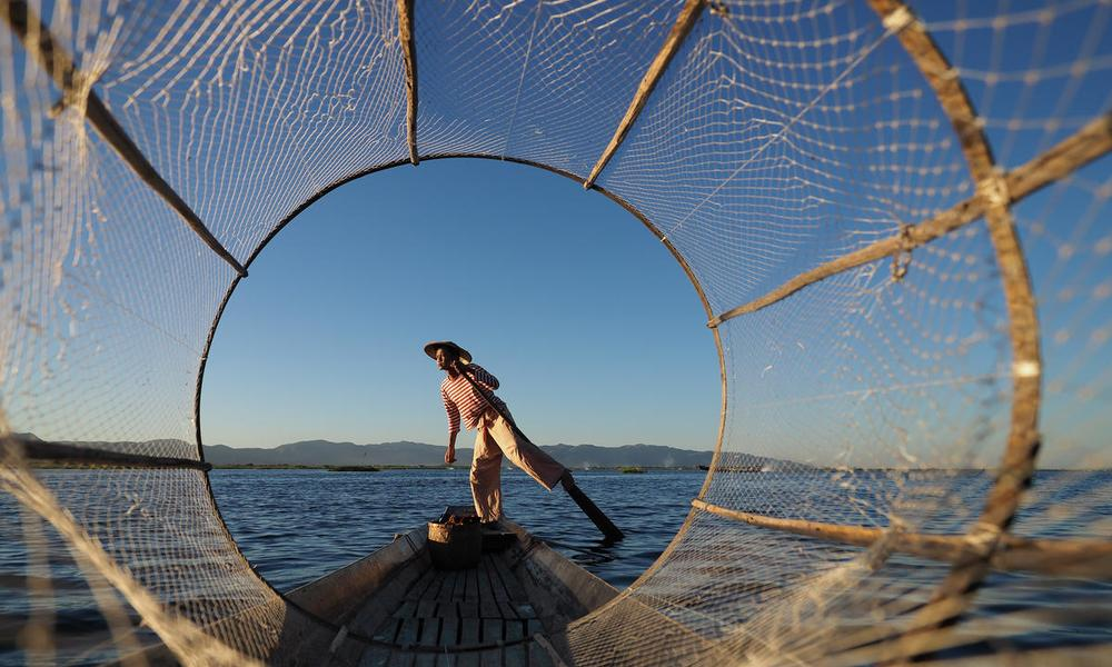 Basket fisherman poses for a frame, Inlay Lake, Myanmar