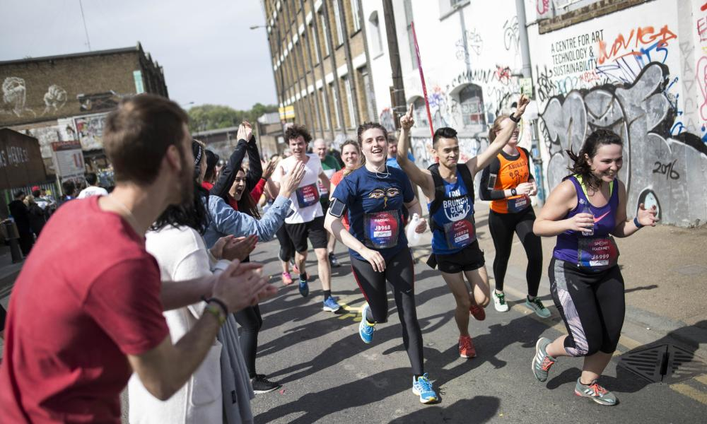 Runners are being cheered on as they go past a street in Hackney with graffitis