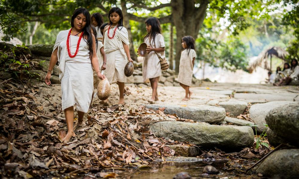 Kogi children walking along a small stream in the Tayrona National Park of Colombia.