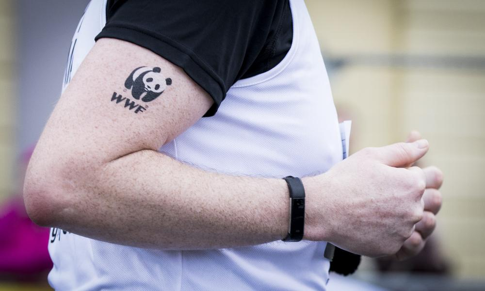 A close up on a runner's arm with a WWF tattoo on his bicep