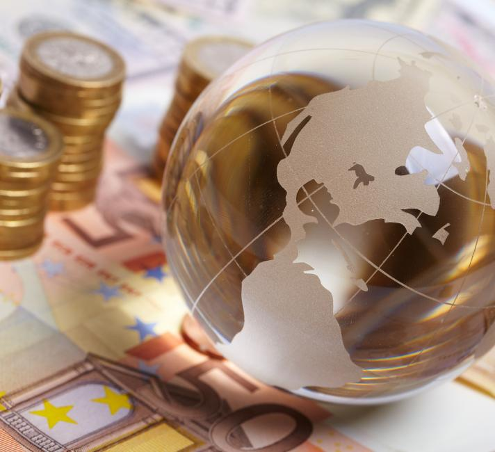 Currency and planet on a table representing global economy - © Shutterstock