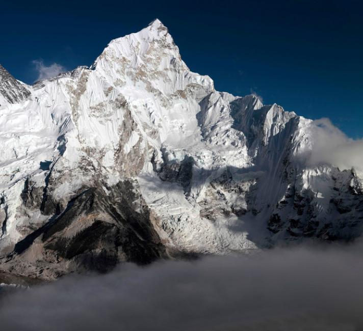 Mount Everest in the Everest Range of the Himalayas in Nepal. Everest is the peak to the left of the picture with snow blowing off its top.