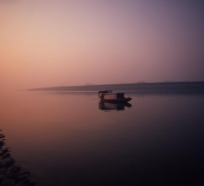 A fishing boat on Dongting Lake at dawn. Hunan Province China.