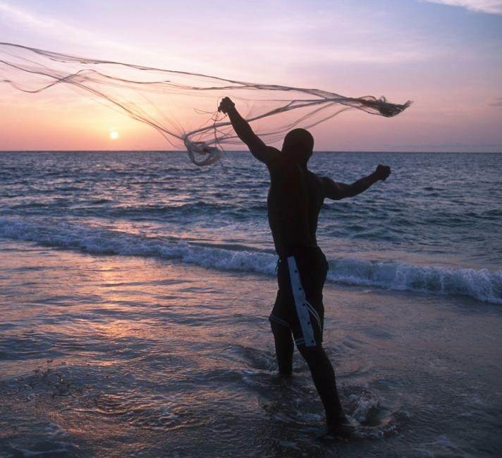 A fisherman casts his fishing net