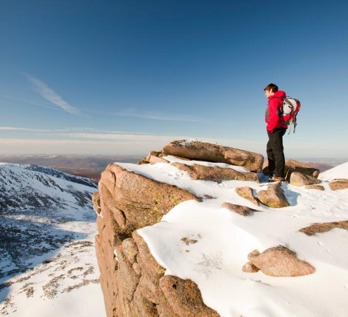 A mountaineer on a rocky granite outcrop above Coire an Lochain in the Cairngorm Mountains, Scotland, UK.