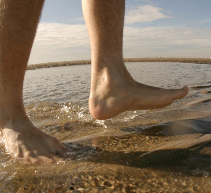 Man's bare feet walking in the water
