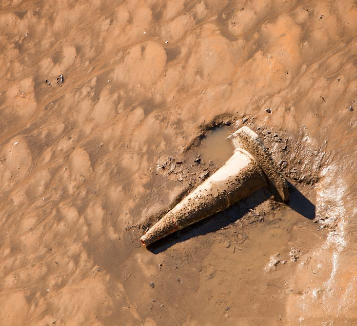 Rubbish thrown into intertidal mud on the side of the river Tees at Middlesbrough, Teeside, UK.