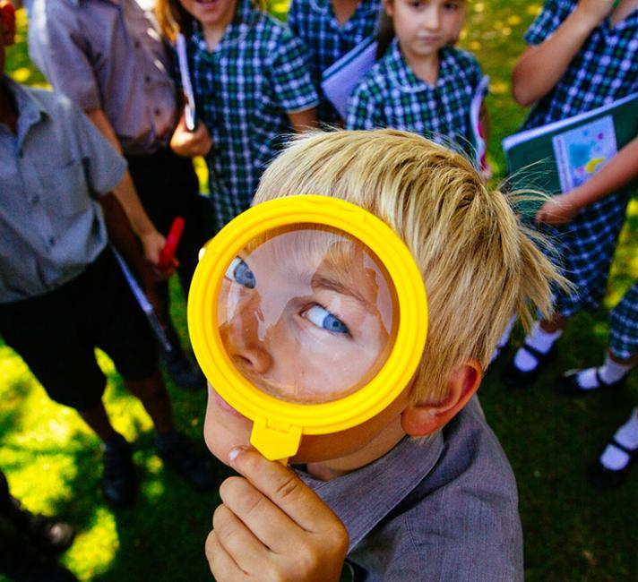 A boy looks through a magnifying glass. Him and his schoolmates have been working with WWF to learn more about nature in their school