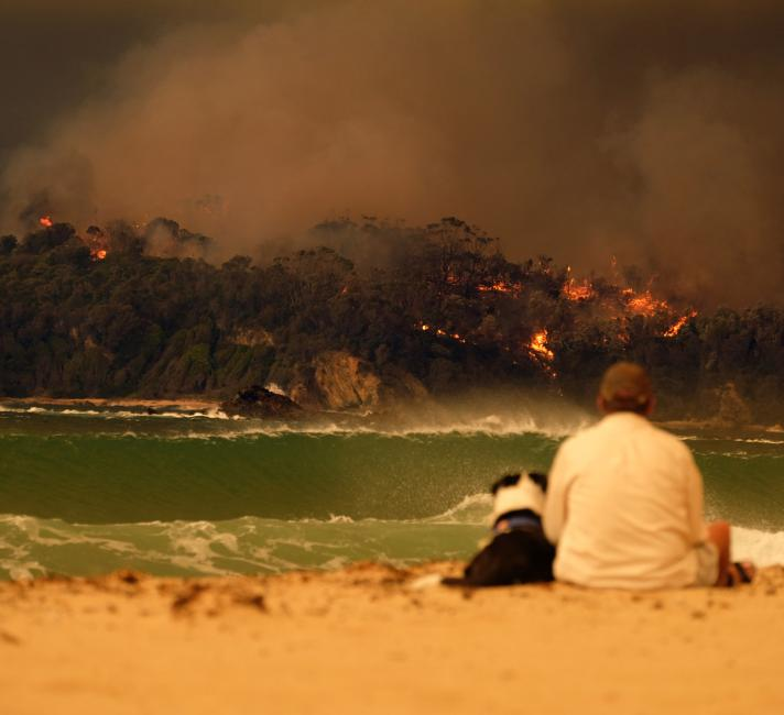 Locals on the beach as a bushfire hits Malua Bay, New South Wales.