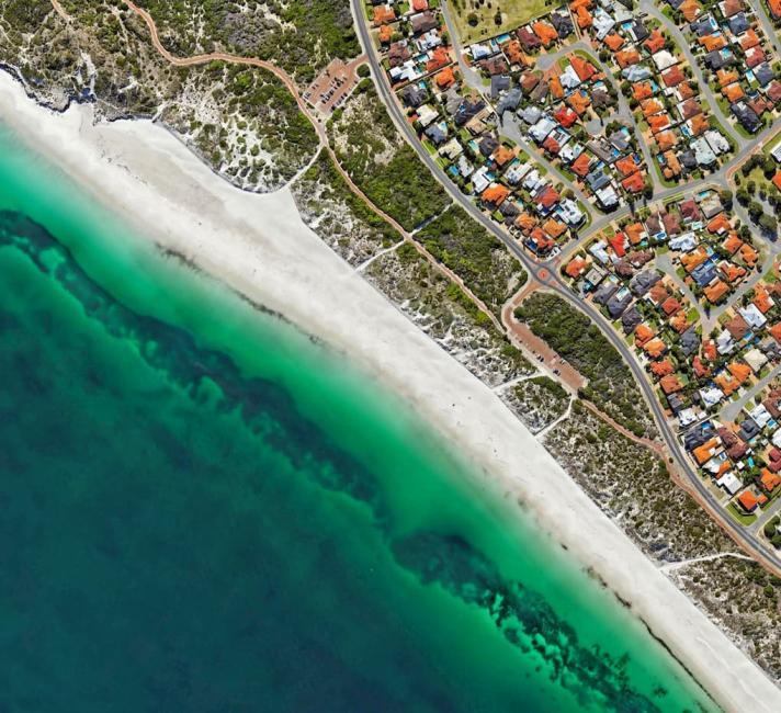 An aerial photograph of houses along the coastline.