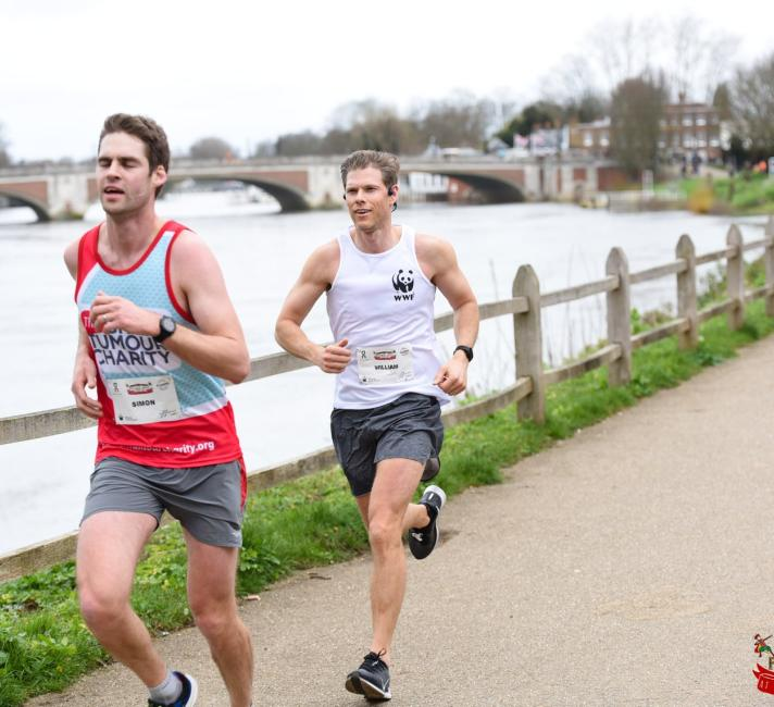 Two white males running alongside the river Thames on a winter morning