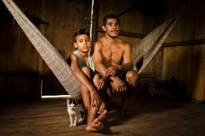 A man and boy sit on a hammock in CazumbÌÁ-Iracema Extractive Reserve in Acre, Brazil. The CazumbÌÁ-Iracema Extractive Reserve is part of the Amazon Region Protected Area program.