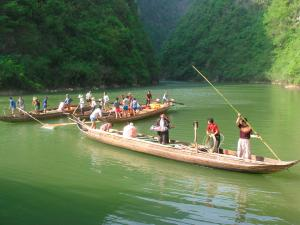 Tujia boatmen steering canoes through a gorge