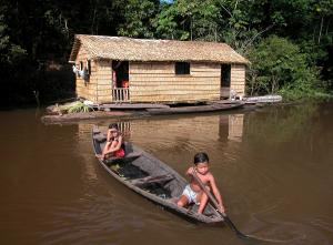 Children in a canoe beside their house made of Babassu straw (Orbygnia phalerata) in the Amazon Upland Rainforest