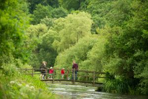 A family cross a bridge, River Itchen, Hampshire, UK